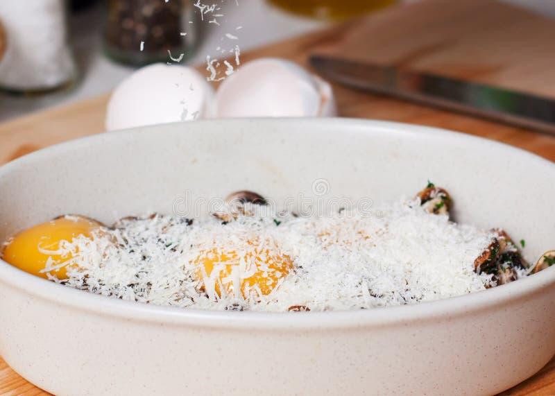 Prato de cozimento com cogumelos, os ovos crus e Parmesão raspado imagens de stock royalty free