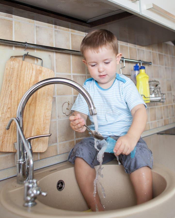 Prato de lavagem do menino engraçado da criança na cozinha fotos de stock royalty free