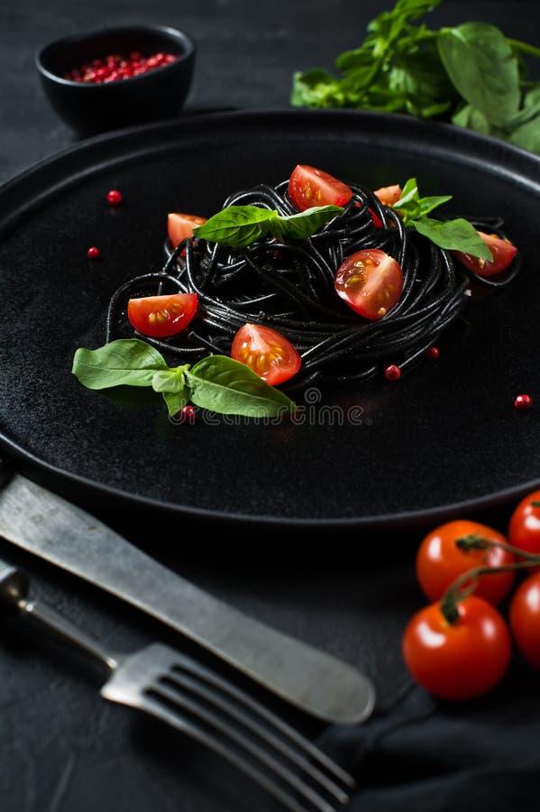 Prato de vegetariano, espaguetes pretos com manjeric?o e tomates de cereja Fundo preto, vista superior fotos de stock