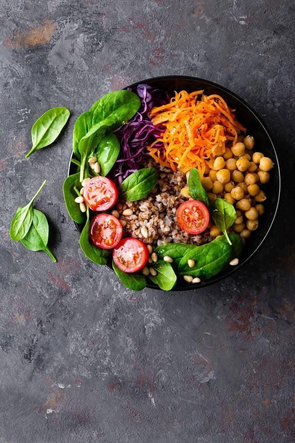Prato de vegetariano saudável com trigo mourisco e salada vegetal do grão-de-bico, da couve, da cenoura, de tomates frescos, de f imagem de stock royalty free