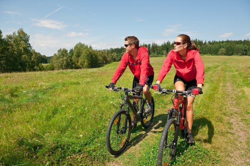 prato delle coppie della bici che guida estate allegra fotografie stock libere da diritti