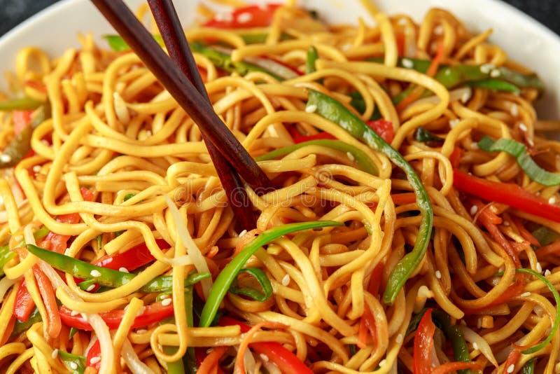 Prato do mein, dos macarronetes e dos vegetais da comida com hashis de madeira imagens de stock