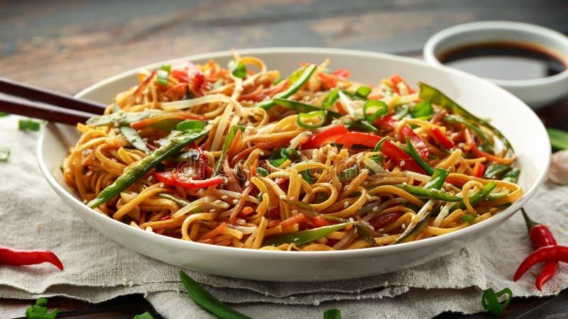 Prato do mein, dos macarronetes e dos vegetais da comida com hashis de madeira foto de stock