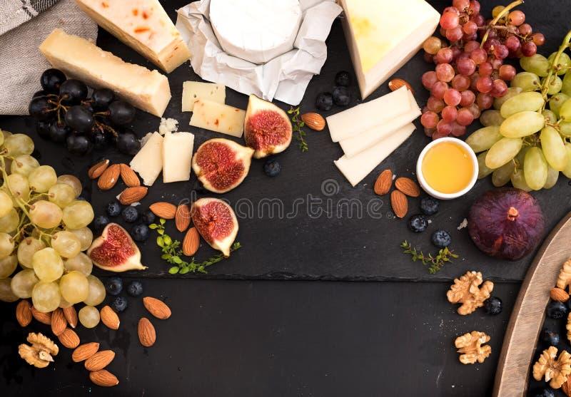 Prato do queijo do gosto com frutos, bagas no cheeseboard preto velho Alimento para o vinho e romântico, guloseimas do queijo Pro fotografia de stock royalty free