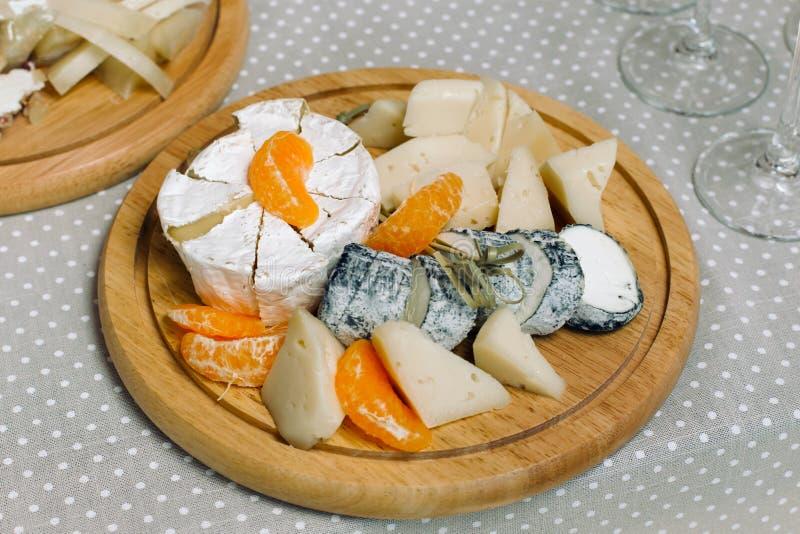 Prato do queijo do gosto em uma placa de madeira foto de stock