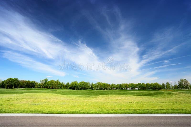 Prato e cielo blu verdi con la strada asfaltata fotografia stock