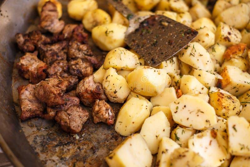 Prato enorme com as salsichas e o assado fritados das batatas Alimento da rua foto de stock