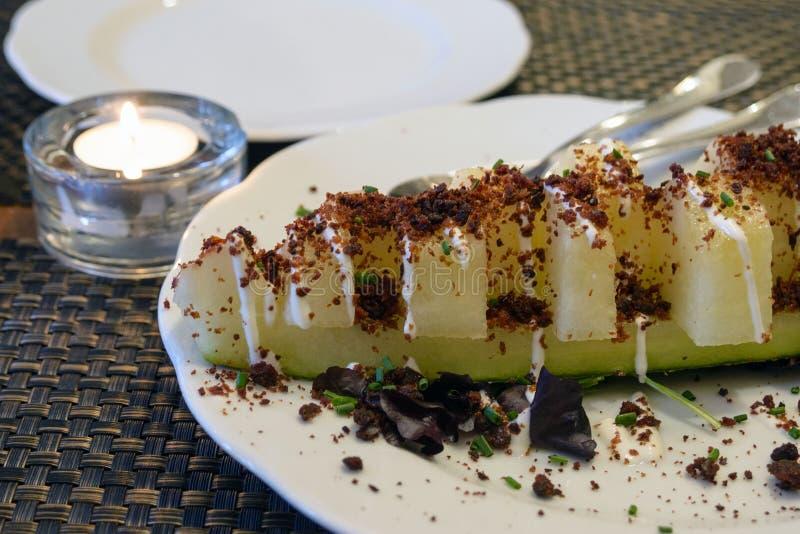 Prato incomum delicioso em um restaurante português Fatias suculentas de melão doce, polvilhadas com o chouriço fritado da salsic imagem de stock royalty free