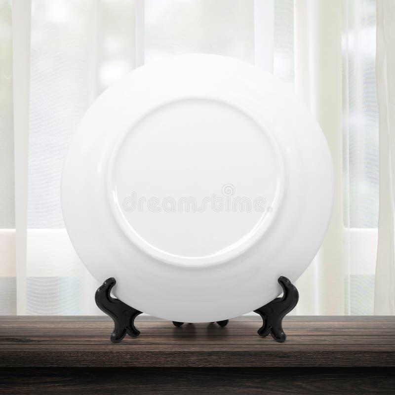 Prato limpo ou placa cerâmica no fundo moderno da cozinha com conceito vazio do dishware Lugar branco do molde do prato na tabela imagens de stock