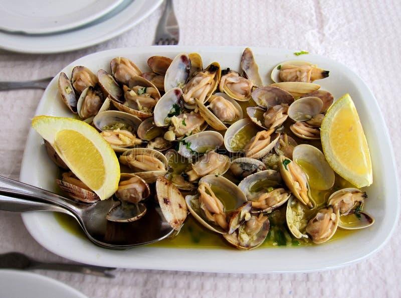 Prato português tradicional, moluscos com alho, azeite virgem extra e limão fotografia de stock