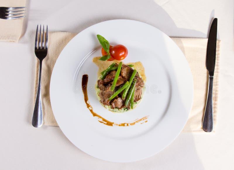 Prato principal Meaty decorado gourmet na placa fotografia de stock