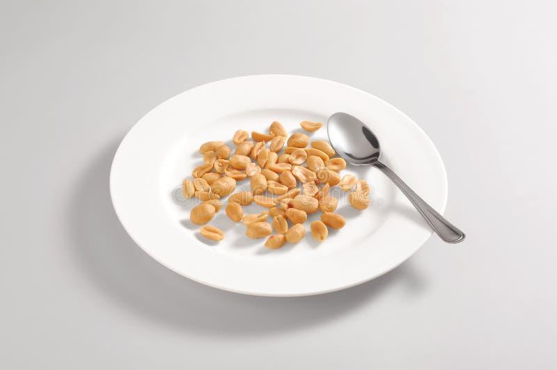 Prato redondo com amendoins salgados imagem de stock