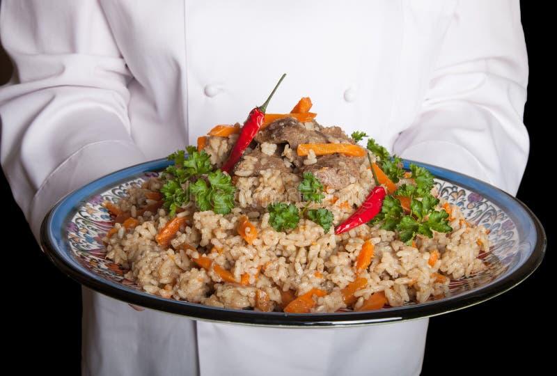 Prato turco com pilau nas mãos do cozinheiro fotografia de stock