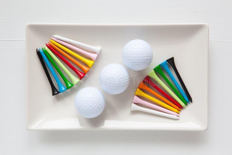 Pratos cerâmicos brancos com bolas de golfe e os T de madeira foto de stock