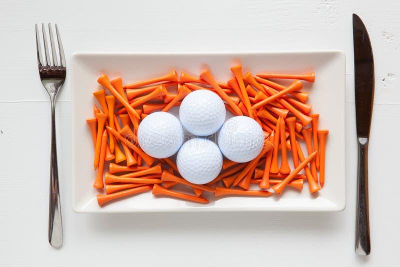 Pratos cerâmicos brancos com bolas de golfe e os T de madeira fotos de stock royalty free