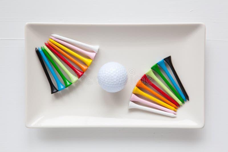 Pratos cerâmicos brancos com bolas de golfe e os T de madeira imagens de stock royalty free