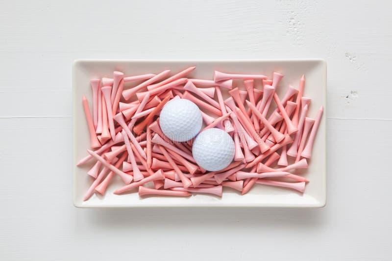 Pratos cerâmicos brancos com bolas de golfe e os T de madeira fotos de stock