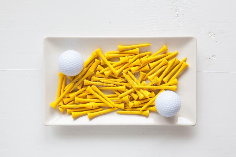 Pratos cerâmicos brancos com bolas de golfe e os T de madeira foto de stock royalty free