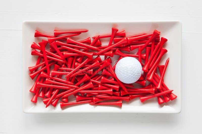Pratos cerâmicos brancos com bolas de golfe e os T de madeira imagem de stock royalty free