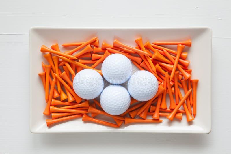 Pratos cerâmicos brancos com bolas de golfe e os T de madeira fotografia de stock royalty free