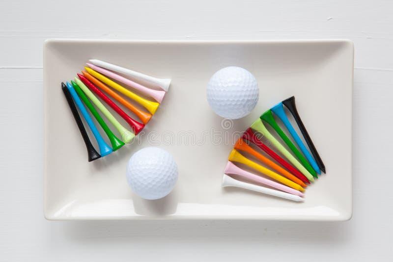 Pratos cerâmicos brancos com bolas de golfe e os T de madeira imagem de stock