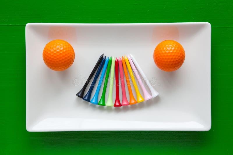 Pratos cerâmicos brancos com os T de madeira do golfe foto de stock