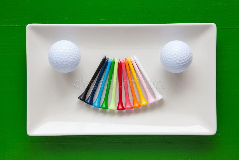 Pratos cerâmicos brancos com os T de madeira do golfe fotografia de stock