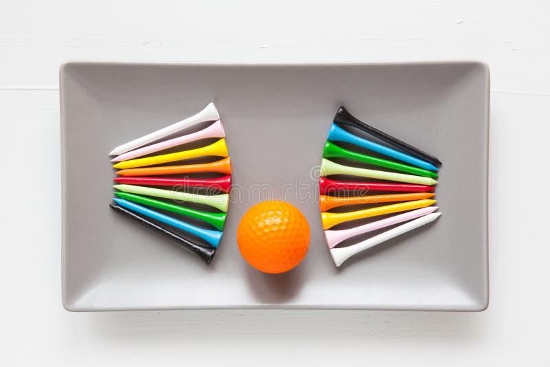 Pratos cerâmicos cinzentos com bolas de golfe e os T de madeira fotografia de stock royalty free