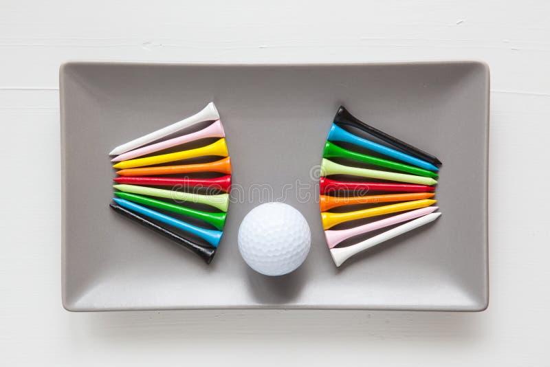 Pratos cerâmicos cinzentos com bolas de golfe e os T de madeira imagens de stock