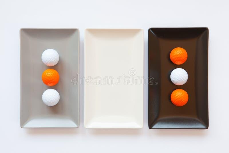 Pratos cerâmicos diferentes com bolas de golfe imagens de stock royalty free