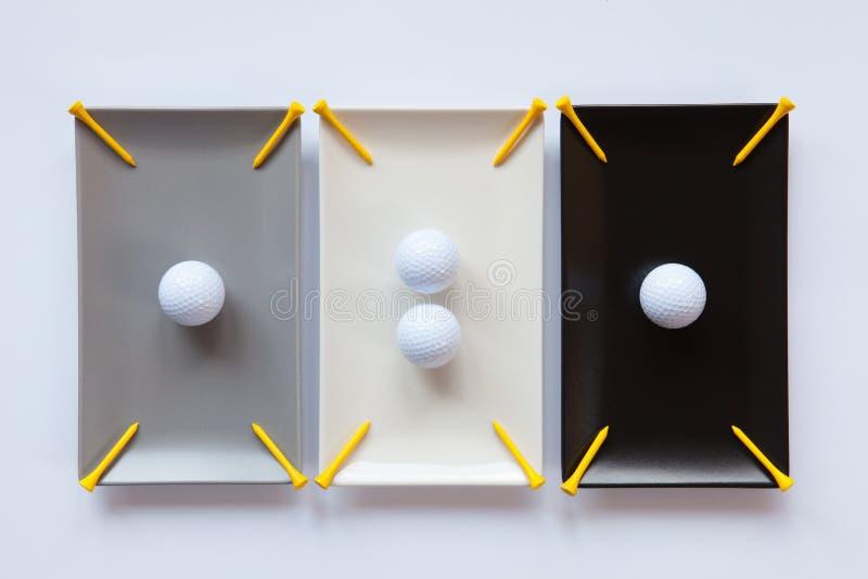Pratos cerâmicos diferentes com bolas de golfe imagem de stock royalty free