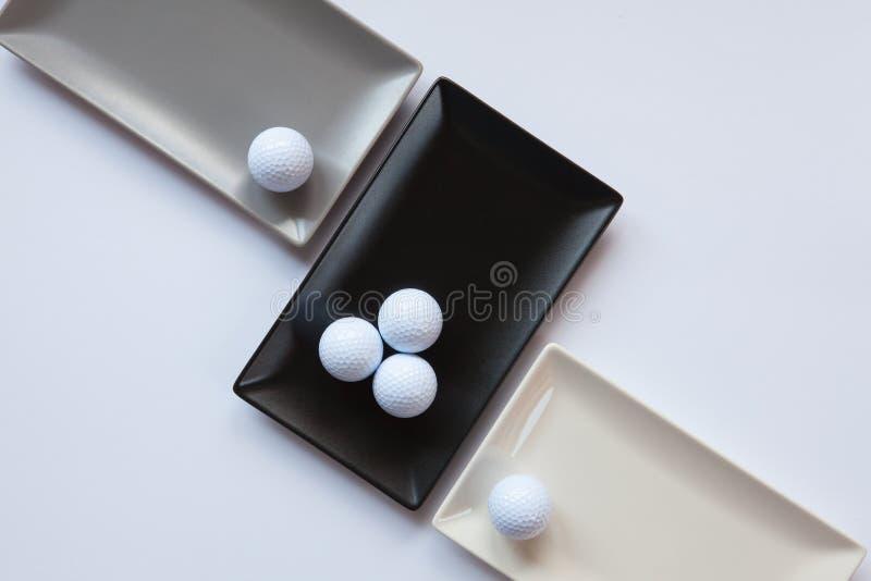 Pratos cerâmicos diferentes com bolas de golfe sobre sobre o backgroun branco fotos de stock royalty free
