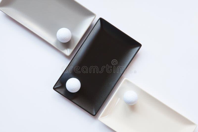 Pratos cerâmicos diferentes com bolas de golfe sobre sobre o backgroun branco imagens de stock
