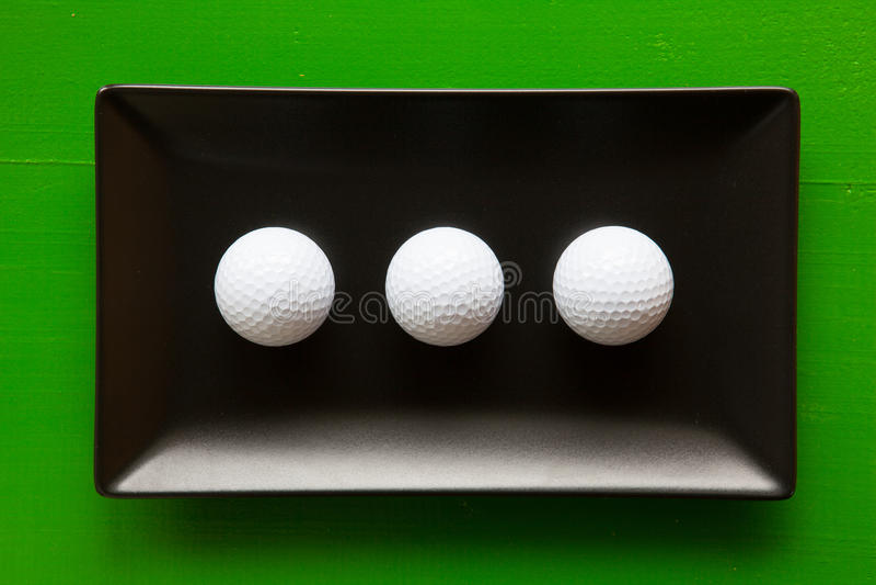 Pratos cerâmicos pretos com bolas de golfe brancas imagens de stock royalty free