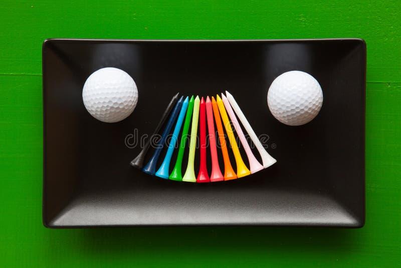 Pratos cerâmicos pretos com bolas de golfe e os T de madeira fotografia de stock