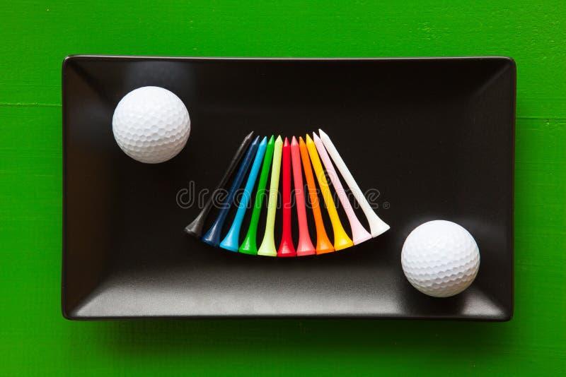 Pratos cerâmicos pretos com bolas de golfe e os T de madeira fotos de stock royalty free