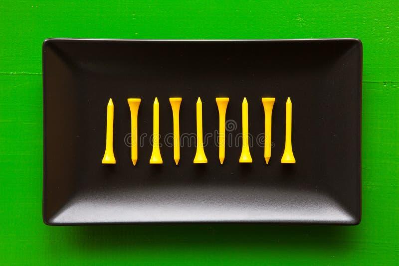 Pratos cerâmicos pretos com bolas de golfe e os T de madeira foto de stock royalty free