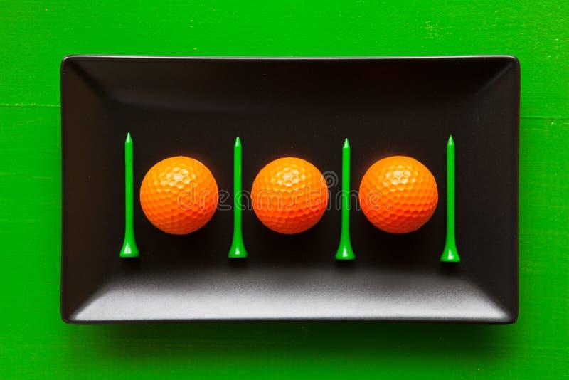 Pratos cerâmicos pretos com bolas de golfe e os T de madeira imagem de stock royalty free