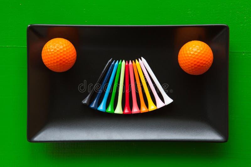 Pratos cerâmicos pretos com bolas de golfe e os T de madeira foto de stock