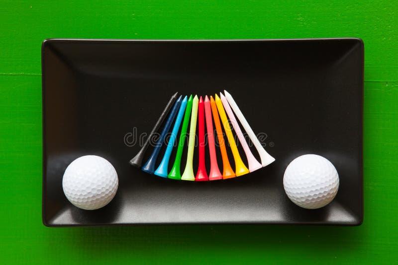 Pratos cerâmicos pretos com bolas de golfe e os T de madeira fotografia de stock royalty free