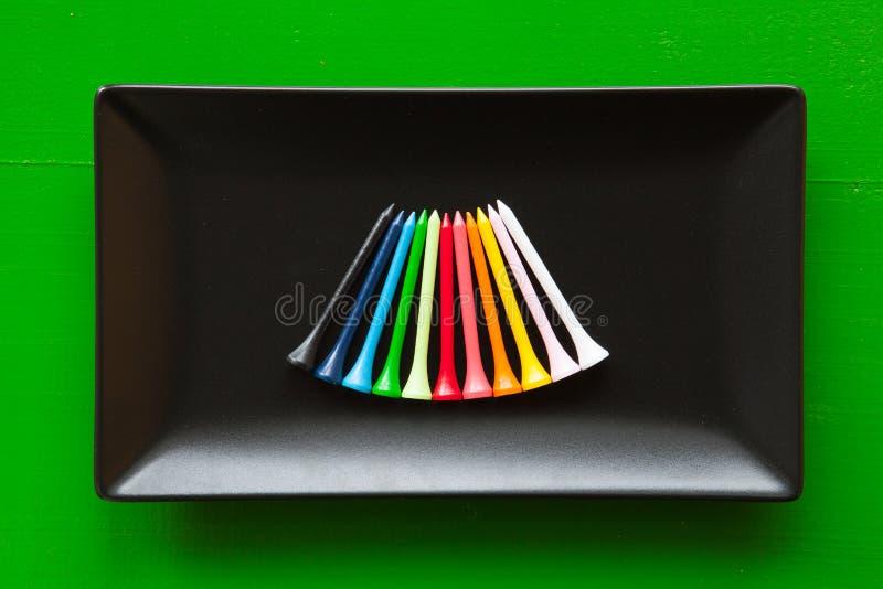 Pratos cerâmicos pretos com os T de madeira do golfe imagens de stock