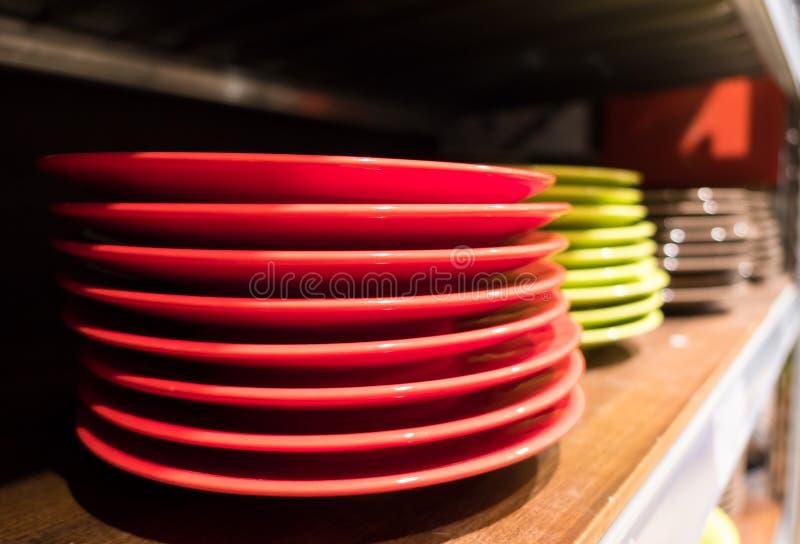 Pratos coloridos em uma estante de madeira fotografia de stock