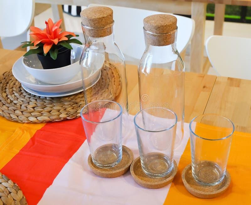 Pratos com a garrafa de vidro e de vidro na tabela fotografia de stock