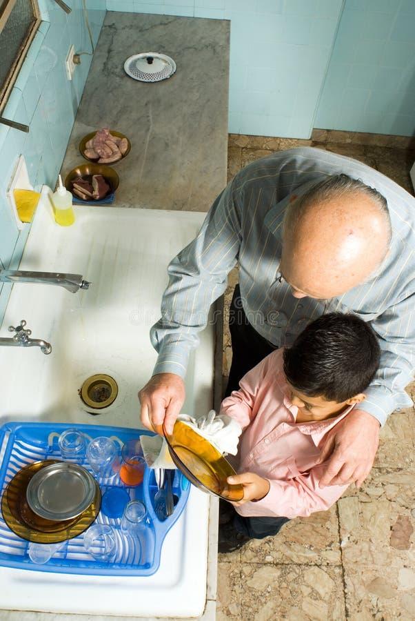 Pratos da lavagem do avô e do neto. Fim acima - H imagens de stock