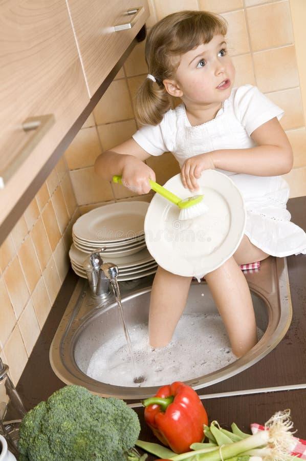 Pratos de lavagem da menina fotos de stock