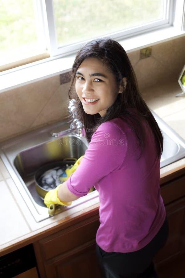 Pratos de lavagem da menina adolescente no dissipador de cozinha fotografia de stock royalty free