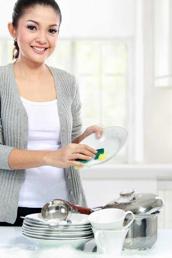 Pratos de lavagem da mulher asiática foto de stock
