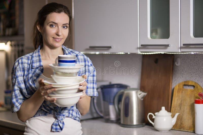 Pratos de lavagem da mulher na cozinha fotografia de stock royalty free