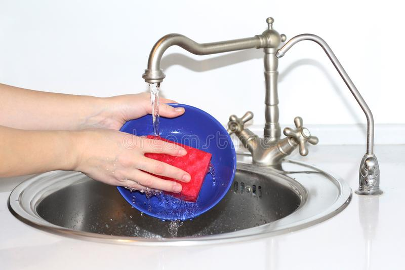 Pratos de lavagem da mulher no dissipador Tem uma esponja de limpeza em sua mão imagens de stock royalty free
