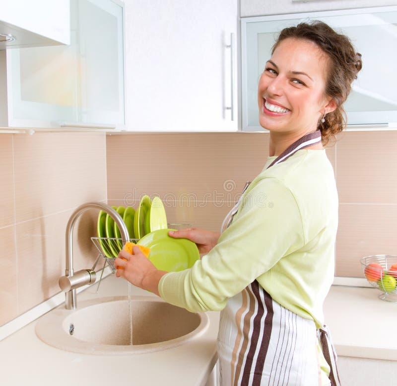 Pratos de lavagem da mulher nova imagens de stock